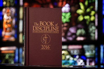 Photo shows the 2016 Book of Discipline in front of a church's stained glass windows. Credit: Mike DuBose, UMNS