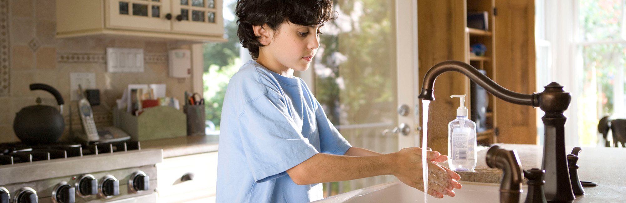 Boy washes hands.