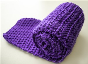 Photo shows rolled-up bright purple scarf.